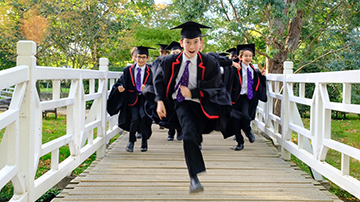 A group of grinning boys in robes run towards the camera across a white footbridge